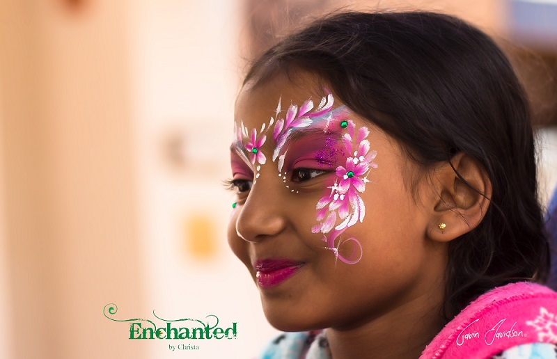This flower fairy princess face paint design has a spray of small flowers on the side of the face and flower petals on the forehead