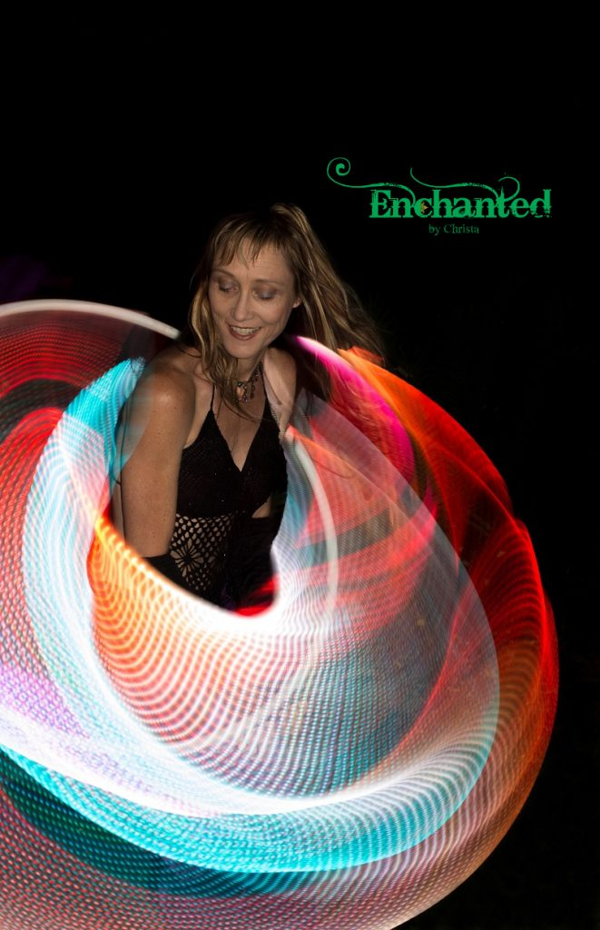 a colourful circle created around the shoulders of the hoop dancer during a LED show. www.enchantedbychrista.co.za
