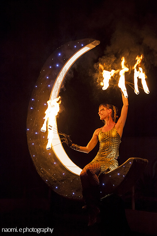 a Fire dancer with fire fingers sitting in a half moon prop designed by Con Grazia. www.enchantedbychrista.co.za