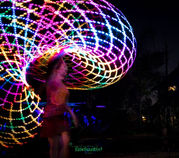 The hula hoop dancer creates a swirling rainbow pattern with a LED hula hoop during a LED hula hoop show. www.enchantedbychrista.co.za