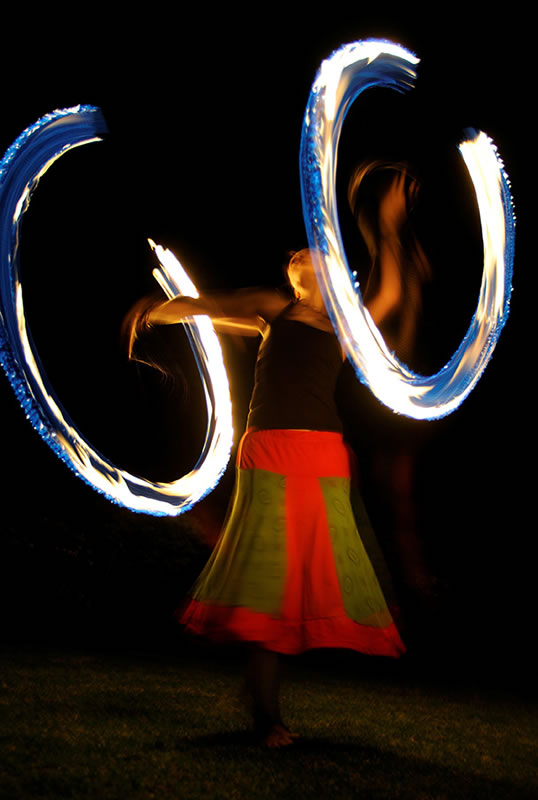 a fire dancer swinging fire poi in a circular motion to create these fire circles