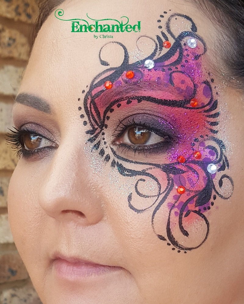 A delicate face paint design around one eye done for a masquerade ball themed year-end function