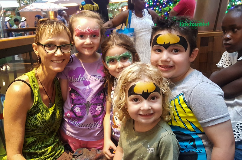 a group of kids with the face painter after they've had their faces painted as batmans and princesses