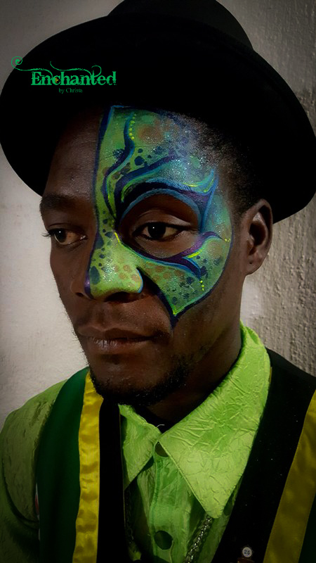 an alien mask face paint design painted around the one eye of an adult performer for a show on New Year's Eve at Suncity Holiday Resort, South Africa