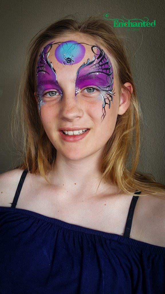 a Different kind of halloween face paint design in shades of purple with spiderwebs and a spider hanging over a full moon.