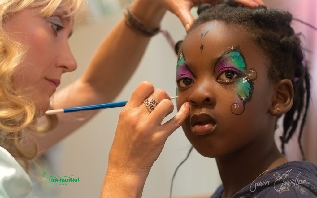 Christa dressed as Alice painting a butterfly design on a girls face at Suncity Holiday Resort, South Africa. www.enchantedbychrista.co.za