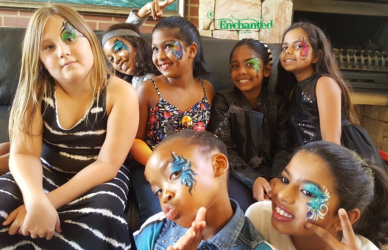 a group of young girls loving their face paint designs around the eyes. The theme for this party was rockstars
