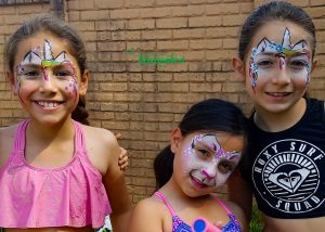 2 girls with unicorn face paint designs and another one with a cat face paint design. www.enchantedbychrista.co.za