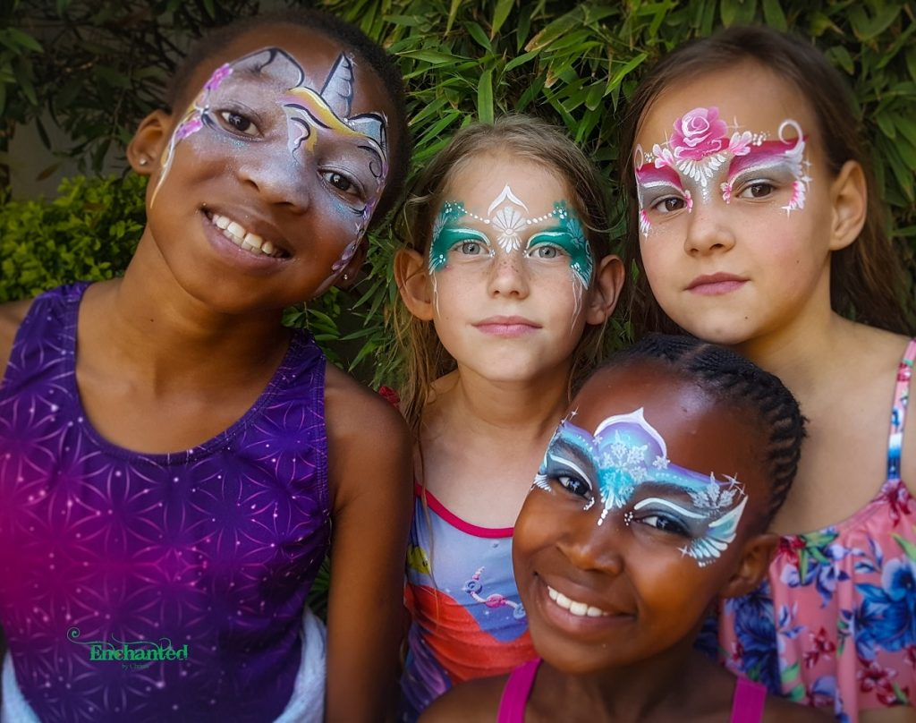 a group of girls with a unicorn, a rose princess, a mermaid and Frozen Elsa face paint designs. www.enchantedbychrista.co.za
