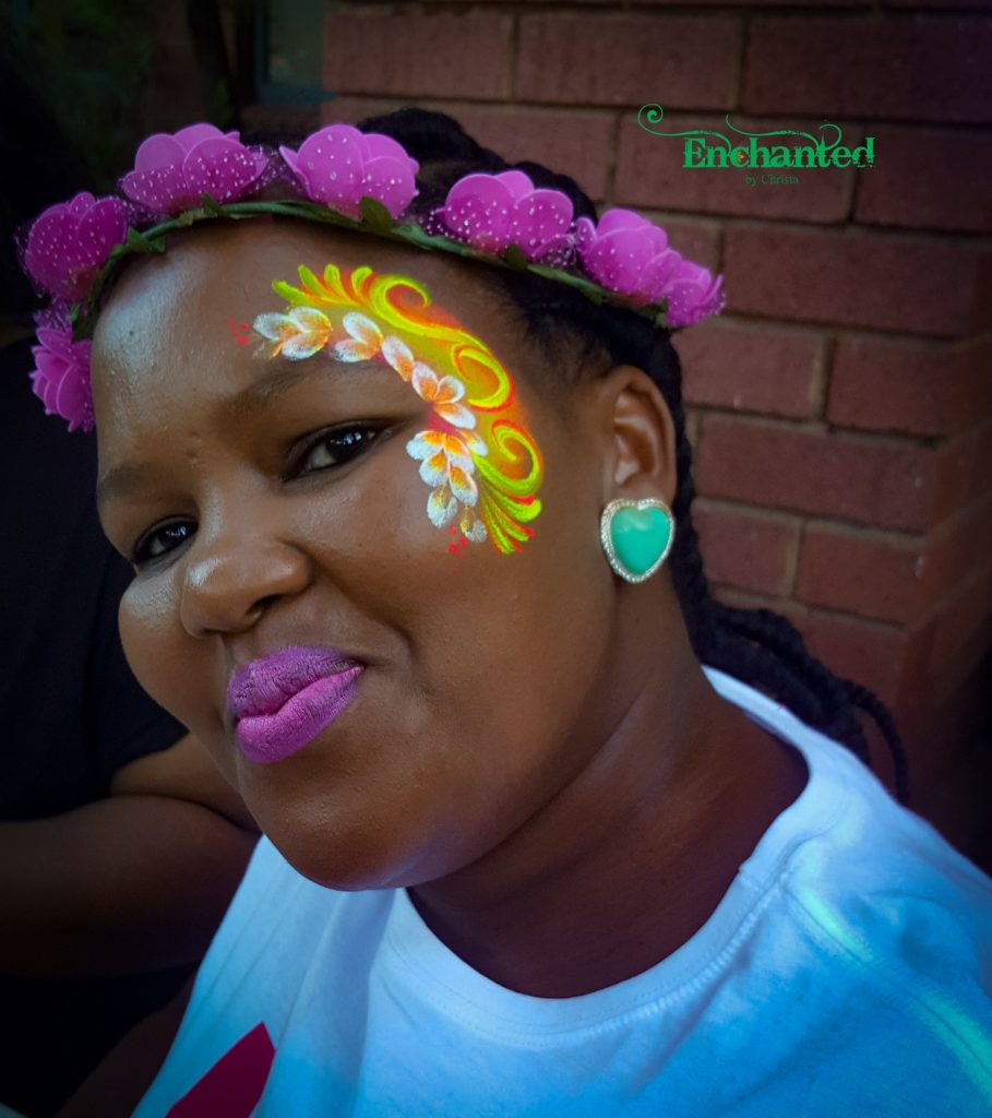 This floral face paint design for women works well even in the day because the UV face paint is so bright