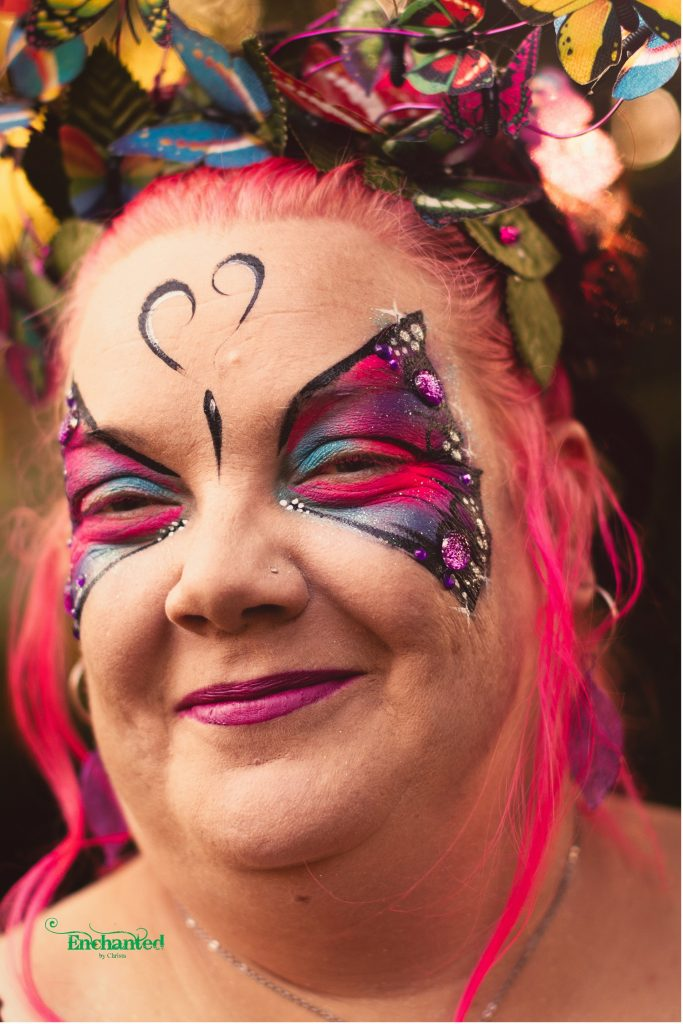 an elegant adult butterfly face paint design with big diamantes matches her butterfly headpiece