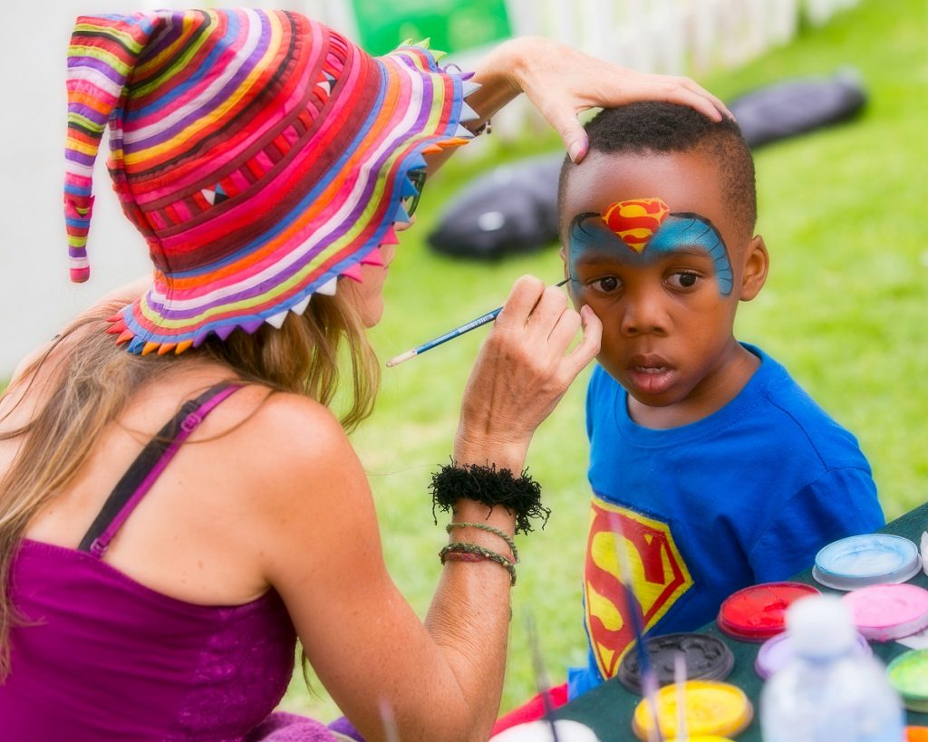 Christa painting a Superman face paint design in blue, red and yellow on a boy at his birthday party