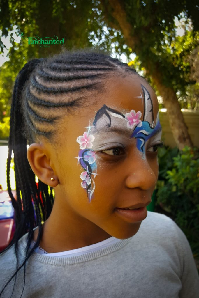 Unicorn face paint design with delicate white and pink flowers to frame the face