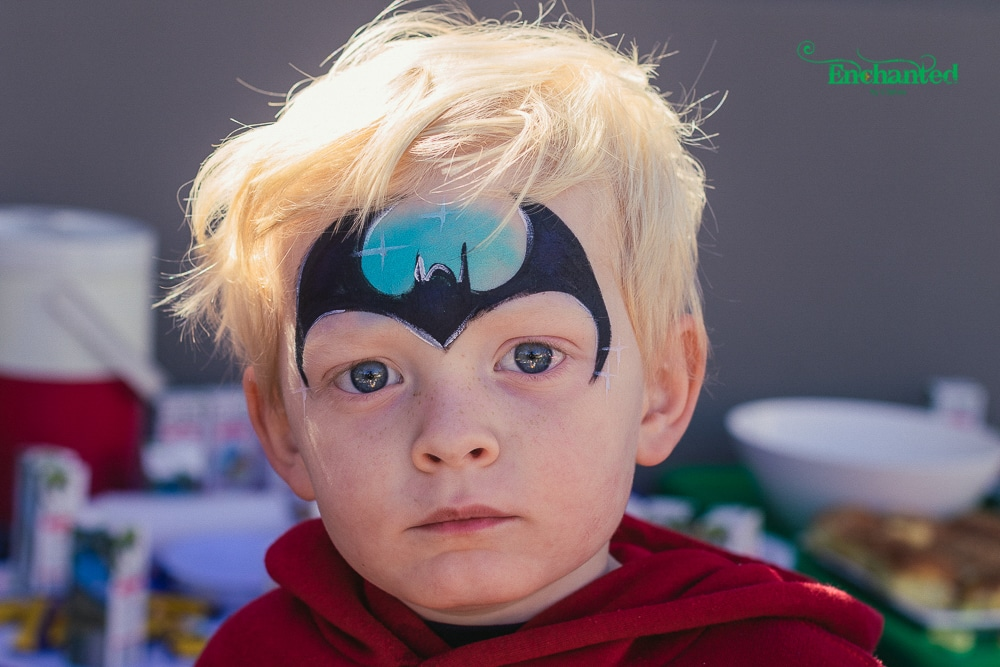 a simple Batman face paint design for small boys. Image captured by our professional birthday photographer as part of our photographer and face painter combo package.