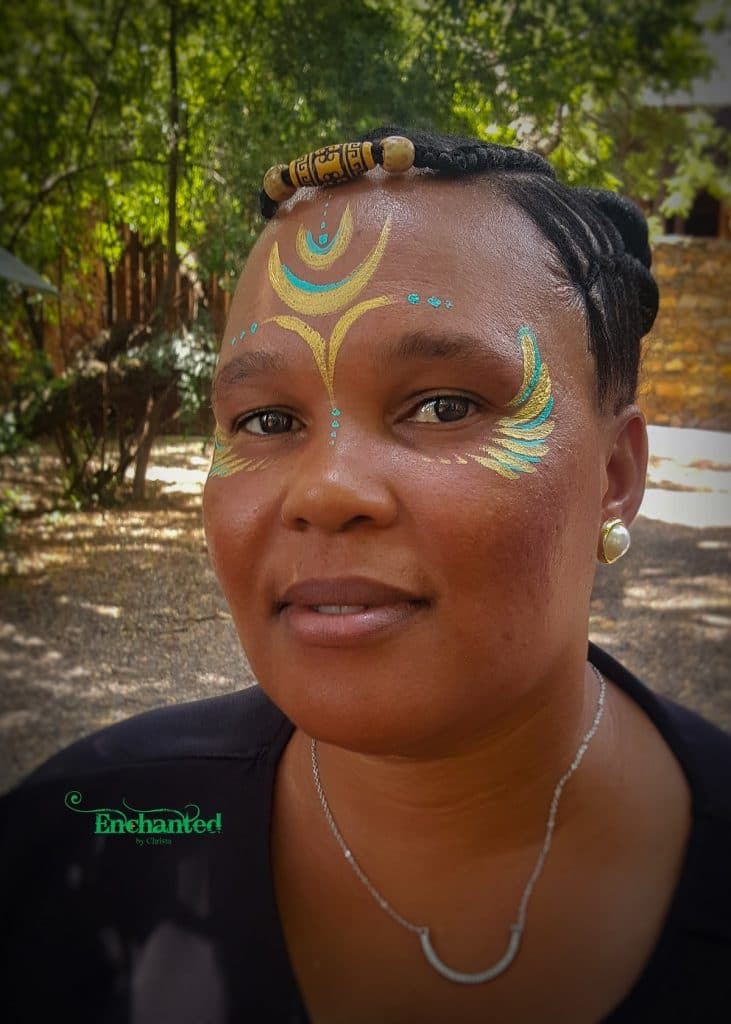 This African Goddess face paint design in gold and blue looked amazing on this lady's dark skin