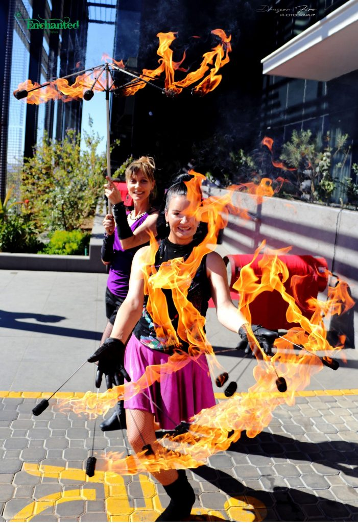 Beautiful female duo show with fire umbrella and fire fingers