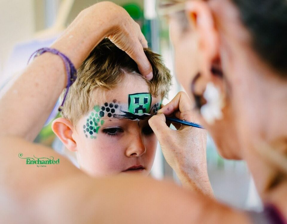 a close-up picture taken by our in house photographer of Christa painting a minecraft design on a boys face