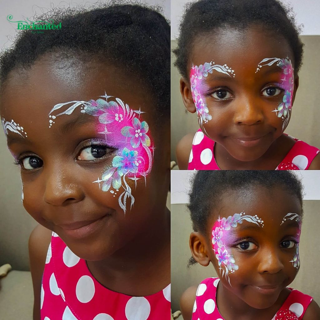 a delicate flower face paint design with a bright pink background frames both eyes of this little girl