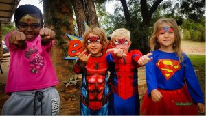 a group of kids with some of the most popular superhero face paint designs like Wonder Woman, Spiderman and Supergirl