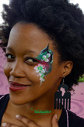 a pretty design with flower petals painted on the side of this ladies face at a corporate event in Johannesburg